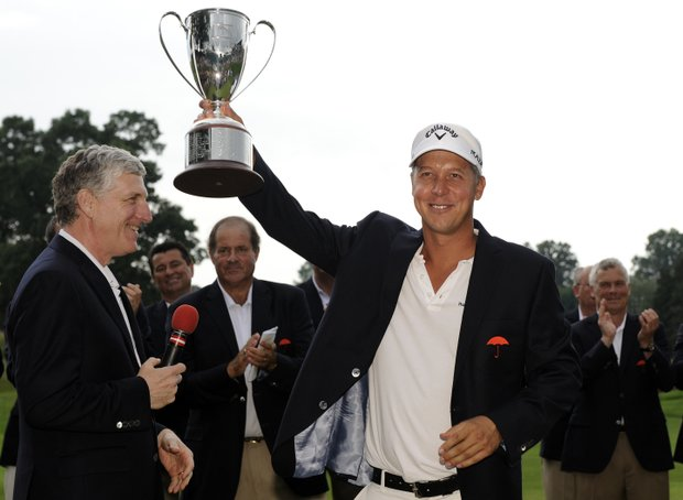 Frederik Jacobson, of Sweden, receives his championship trophy from Travelers chief executive Jay Fishman, left, after winning the Travelers Championship golf tournament in Cromwell, Conn., on Sunday, June 26, 2011. Jacobson's 20-under par victory was his first on the PGA tour.