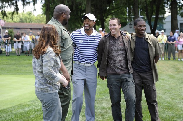 Tiger Woods shares a laugh with members of 4Troops who sang the national anthem for the opening ceremonies of the AT&T National golf tournament at Aronimink Golf Club, Wednesday, June 29, 2011, in Newtown Square, Pa.