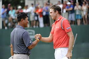 Nick Watney, right, shakes hands with K.J. Choi after Watney won the AT&T National golf tournament at Aronimink Golf Club, Sunday, July 3, 2011, in Newtown Square, Pa.