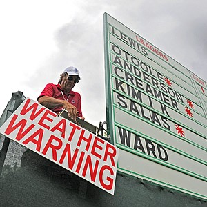 "David Hostetler hangs a ""WEATHER WARNING"" sign from his scoreboard after play was suspended because of lightning during the second round of the Women's U.S. Open golf tournament at the Broadmoor Golf Club on Friday, July 8, 2011, in Colorado Springs, Colo."