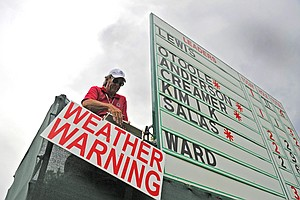 """David Hostetler hangs a """"WEATHER WARNING"""" sign from his scoreboard after play was suspended because of lightning during the second round of the Women's U.S. Open golf tournament at the Broadmoor Golf Club on Friday, July 8, 2011, in Colorado Springs, Colo."""