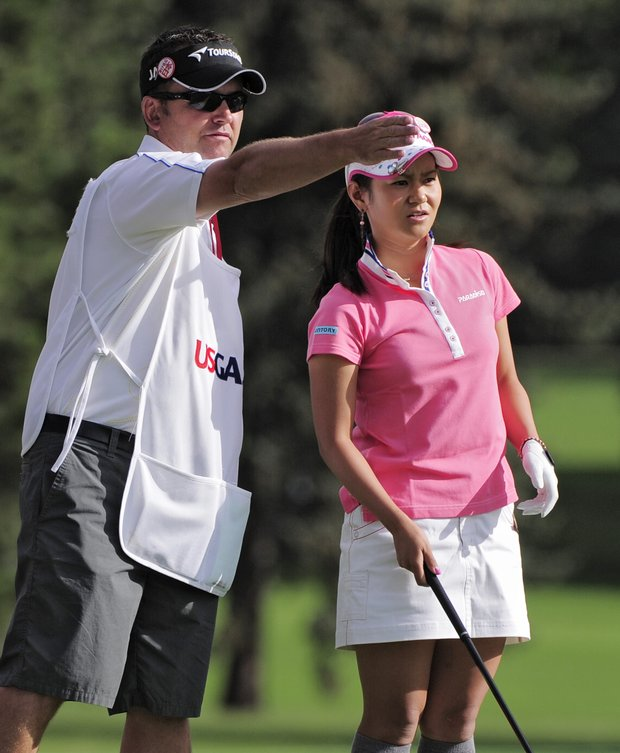Caddy Mick Seaborn points toward the second hole as Ai Miyazato of Japan gets ready to tee off on during the delayed third round of the Women's U.S. Open golf tournament at the Broadmoor Golf Club on Sunday, July 10, 2011, in Colorado Springs, Colo.