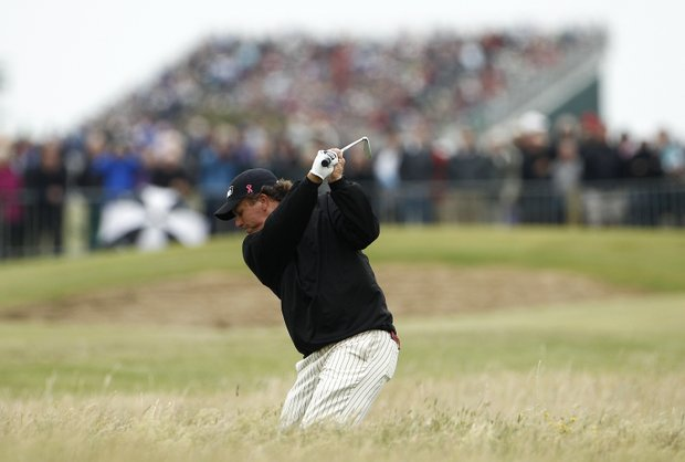Phil Mickelson of the US hits a shot out of the rough on the 6th hole during the first day of the British Open Golf Championship at Royal St George's golf course Sandwich, England, Thursday, July 14, 2011.
