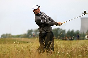 Rory McIlroy hacks out of deep rough on the 15th hole Thursday during the first round of the Open Championship.