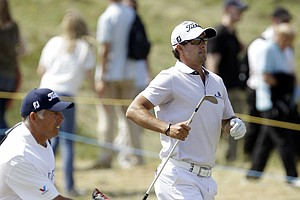 Australia's Adam Scott jumps up on the 9th fairway to watch his shot as his caddie Steve Williams takes his club during the second day of the British Open Golf Championship at Royal St George's golf course Sandwich, England, Friday, July 15, 2011.