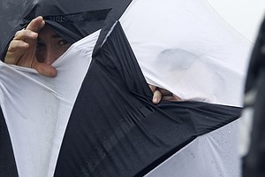 Spectators peer through gaps of an umbrella as they watch play on the third day of the British Open Golf Championship at Royal St George's in Sandwich, England on Saturday.