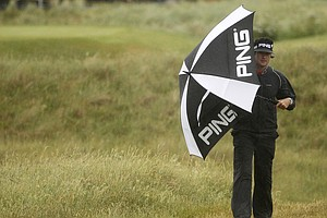 Bubba Watson of the US shelters from the rain as he walks down the 6th fairway during the third day of the British Open Golf Championship at Royal St George's golf course Sandwich, England, Saturday, July 16, 2011.