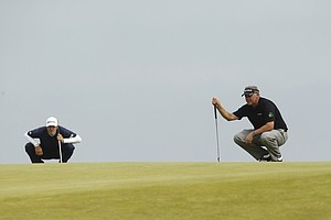 Northern Ireland's Darren Clarke and Dustin Johnson of the US, left, line up their putts on the 10th green during the final day of the British Open Golf Championship at Royal St George's golf course Sandwich, England, Sunday, July 17, 2011.
