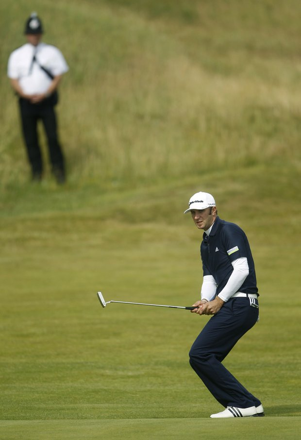 Dustin Johnson of the US watches his shot on the 7th fairway as a policeman looks on during the final day of the British Open Golf Championship at Royal St George's golf course Sandwich, England, Sunday, July 17, 2011.