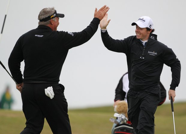 Northern Ireland's Rory McIlroy, right, and Northern Ireland's Darren Clarke react together on the 12th hole during a practice round ahead of the British Open Golf Championship at Royal St George's golf course in Sandwich, England, Wednesday, July 13, 2011.