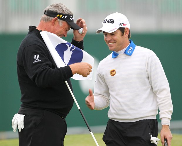 South Africa's Louis Oosthuizen, right and Northern Ireland's Darren Clarke shake hands on the 18th green after a practice round ahead of the British Open Golf Championship at Royal St George's golf course in Sandwich, England, Wednesday, July 13, 2011.