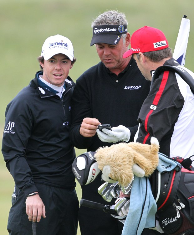 Northern Ireland's Rory McIlroy, left, his caddie JP Fitzgerald, right, and Northern Ireland's Darren Clarke talk on the 7th green during a practice round ahead of the British Open Golf Championship at Royal St George's golf course in Sandwich, England, Wednesday, July 13, 2011.