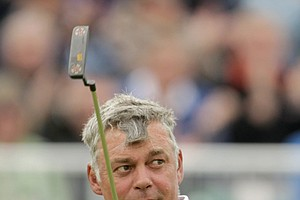 Northern Ireland's Darren Clarke holds up his putter on the 18th green after finishing his round during the first day of the British Open Golf Championship at Royal St George's golf course Sandwich, England, Thursday, July 14, 2011.