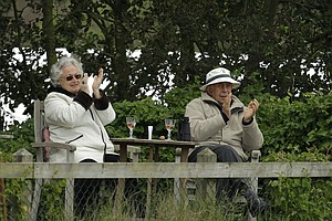 Local residents sit in their garden and watch the play on the 4th green during the final day of the British Open Golf Championship at Royal St George's golf course Sandwich, England, Sunday, July 17, 2011.