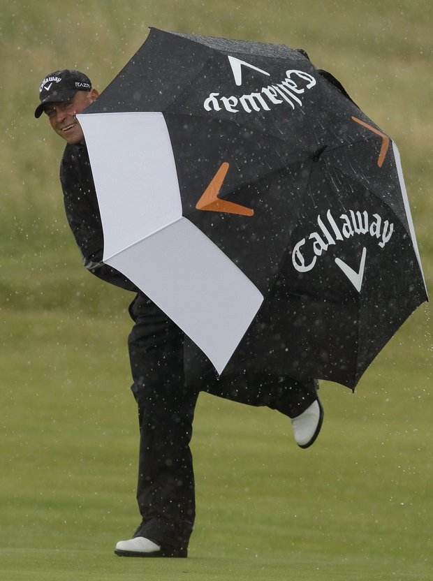 Denmark's Thomas Bjorn tries to shelter from the rain on the 8th green during the final day of the British Open Golf Championship at Royal St George's golf course Sandwich, England, Sunday, July 17, 2011.