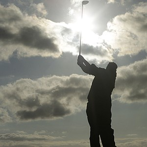 A silhouetted Darren Clarke of Northern Ireland hits a shot off the 18th tee during the third day of the British Open Golf Championship at Royal St George's golf course Sandwich, England, Saturday, July 16, 2011.