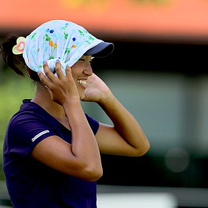 Annie Park puts a cold wet towel on her head while practicing her putting after her Round of 64. Park advanced by defeating Caroline Inglis, 4&3.