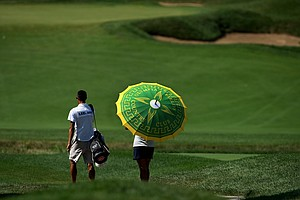 Amy Lee shields herself from the sun with an Olympia Fields umbrella during the Round of 32 at the 63rd U. S. Girls' Junior Championship at Olympia Fields Country Club.