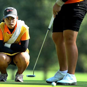Moriya Jutanugarn helps her sister Ariya line up a putt during the Round of 32 at the 63rd U. S. Girls' Junior Championship at Olympia Fields Country Club.