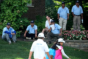 Some of the maintenance crew watch play at No. 11 during the Round of 16 at the 63rd U. S.  Girls' Junior Championship at Olympia Fields Country Club.