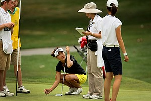 Karen Chung looks to Debbie Mackie for a ruling after the horns were sounded for a weather delay during Quarterfinals. After the horns blew, Yu Liu gave Chung the short putt.