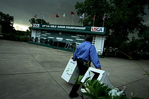 Garbage cans are corralled as a storm approaches during Quarterfinals. Play was suspended at 10 a.m.