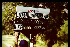 A standard bearer holds a sign indicating the score through 11 holes on Friday.