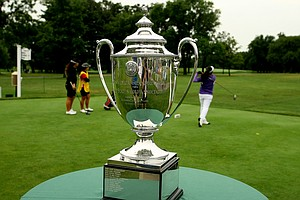 The Glenna Collett Vare tropy for the U. S. Girls' Junior Championship sits at the first tee as Ariya Jutanugarn and Dottie Ardina tee off during the morning round.