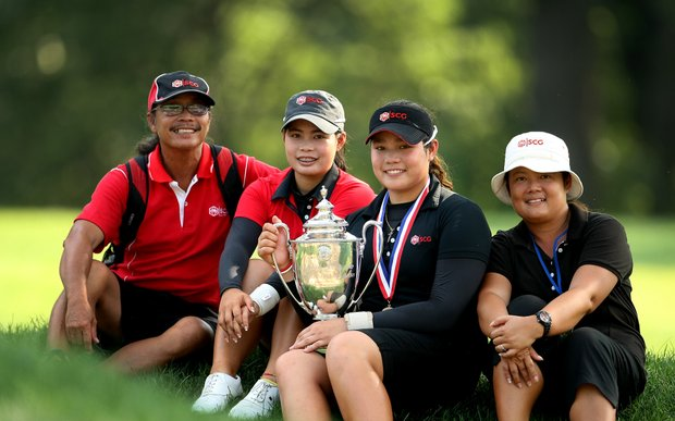 Ariya Jutanugarn, center with trophy, poses with her family, from left, father, Somboon, sister, Moriya and far right her mother, Narumon, after winning the 63rd U. S.  Girls' Junior Championship.