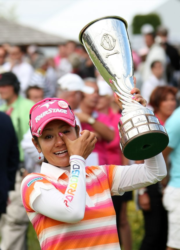 Ai Miyazato of Japan cries as she holds her trophy after winning the Evian Masters women's golf tournament in Evian, eastern France, Sunday, July 24, 2011.