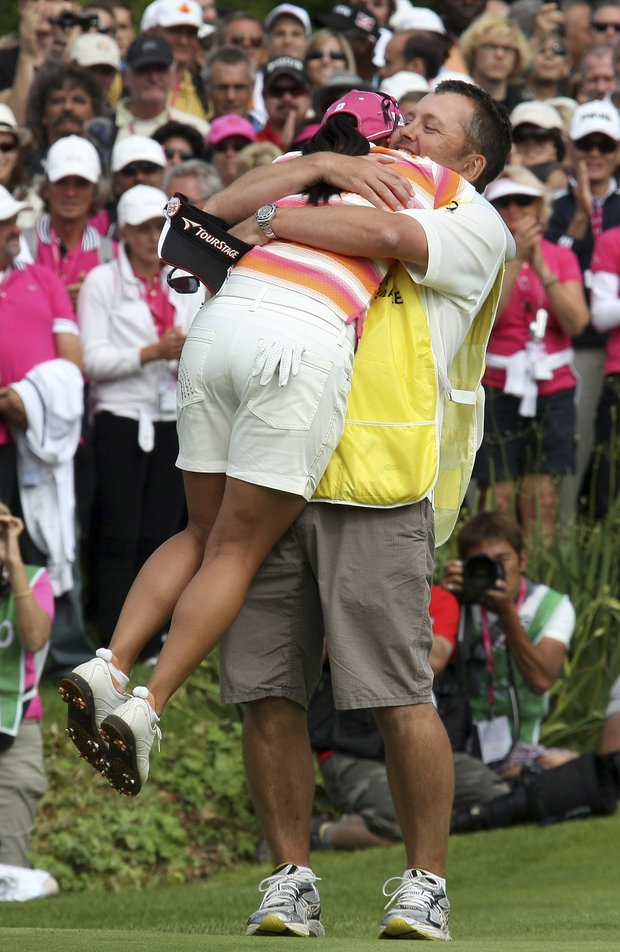 Ai Miyazato of Japan, left, celebrates with her caddie after winning the Evian Masters women's golf tournament in Evian, eastern France, Sunday, July 24, 2011. Ai Miyazato clinched her first title of the year at the Evian Masters on Sunday and pledged to share her prize money with the people still suffering in the aftermath of the disasters back home in Japan.