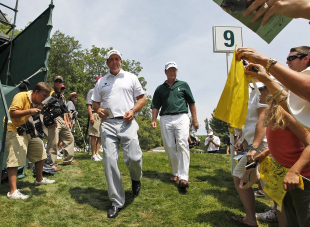 Phil Mickelson, left, and Tom Watson, right, leave the ninth hole after finishing the first round of the Greenbrier Classic golf tournament at the Greenbrier in White Sulphur Springs, W.Va., Thursday, July 28, 2011.