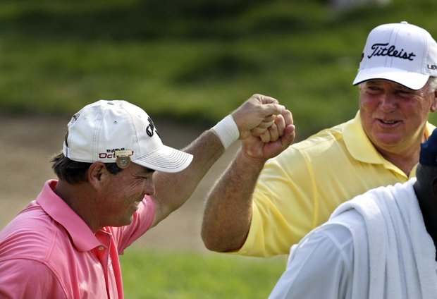 Olin Browne, left, fist bumps Mark O'Meara after they both birdie the 17th hole during the third round of the U.S. Senior Open golf tournament at the Inverness Club in Toledo, Ohio, Saturday, July 30, 2011.