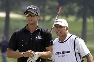 Adam Scott, left, of from Australia, heads to the third green with his caddie Steve Williams during final round play in the Bridgestone Invitational golf tournament at Firestone Country Club in Akron, Ohio, on Sunday, Aug. 7, 2011.