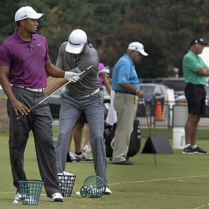 As Tiger Woods, left, watches his shot on the driving range before the first round of the Bridgestone Invitational golf tournament at Firestone Country Club in Akron, Ohio on Thursday, Aug. 4, 2011. Woods' former caddie Steve Williams, second from right, is manning the bag of Adam Scott of Australia.