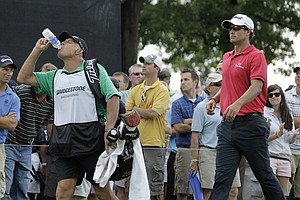 Adam Scott and his caddie Steve Williams head from the 10th tee during first round play in the Bridgestone Invitational golf tournament at Firestone Country Club in Akron, Ohio on Thursday, Aug. 4, 2011.