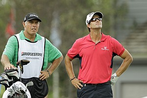 Adam Scott, from Australia, left, waits with caddie Steve Williams on the 18th tee during the first round of the Bridgestone Invitational golf tournament Thursday, Aug. 4, 2011, at Firestone Country Club in Akron, Ohio. Scott finished at 8-under par for a one shot lead.