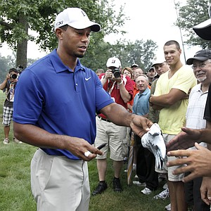 Tiger Woods hands a signed glove to spectator Brady Klotz of Nappanee, Indiana, who he hit with his tee shot off the sixth tee, during third round play in the Bridgestone Invitational golf tournament at Firestone Country Club in Akron, Ohio on Saturday, Aug. 6, 2011.