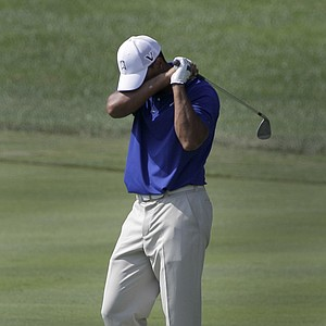 Tiger Woods reacts on the 16th fairway as his fairway shot went into the green side bunker during third round play in the Bridgestone Invitational golf tournament at Firestone Country Club in Akron, Ohio on Saturday, Aug. 6, 2011.