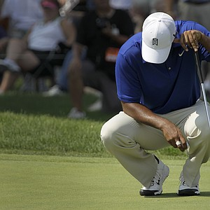 Tiger Woods crouches on the 18th green after missing a putt for par during third round play in the Bridgestone Invitational golf tournament at Firestone Country Club in Akron, Ohio on Saturday, Aug. 6, 2011.