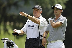 Caddie Steve Williams, left, talks with Adam Scott, from Australia, on the 18th fairway during the third round of the Bridgestone Invitational golf tournament at Firestone Country Club in Akron, Ohio Saturday, Aug. 6, 2011.