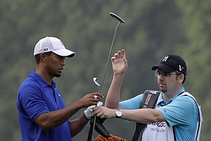 Tiger Woods and his caddie Bryon Bell exchange clubs in the ninth fairway during third round play in the Bridgestone Invitational golf tournament at Firestone Country Club in Akron, Ohio on Saturday, Aug. 6, 2011.