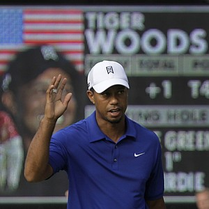 Tiger Woods waves after putting out at the ninth hole during third round play in the Bridgestone Invitational golf tournament at Firestone Country Club in Akron, Ohio on Saturday, Aug. 6, 2011.