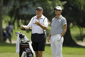 Caddie Steve Williams talks with Adam Scott during the third round of the Bridgestone Invitational golf tournament at Firestone Country Club in Akron, Ohio Saturday, Aug. 6, 2011.