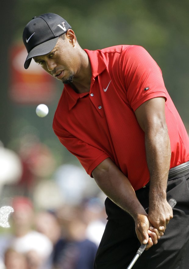Tiger Woods chips to the sixth green during the final round of the Bridgestone Invitational golf tournament at Firestone Country Club in Akron, Ohio, Sunday, Aug. 7, 2011.