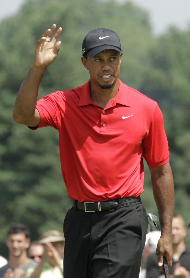 Tiger Woods waves after making birdie on the 17th hole during the final round of the Bridgestone Invitational golf tournament at Firestone Country Club in Akron, Ohio, Sunday, Aug. 7, 2011. Woods finished the tournament at 1 over par.