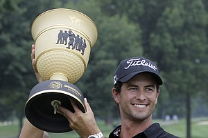 Adam Scott, from Australia, raises the trophy after winning the Bridgestone Invitational golf tournament at Firestone Country Club in Akron, Ohio, on Sunday, Aug. 7, 2011.