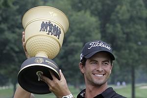 Adam Scott, from Australia, raises the trophy after winning the Bridgestone Invitational golf tournament at Firestone Country Club in Akron, Ohio, on Sunday, Aug. 7, 2011.
