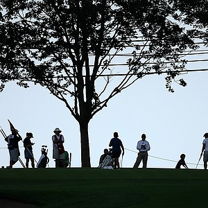 Players, caddies and officials are silhouetted against the sky at No. 14 during Monday stroke play.