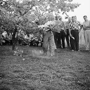 Arnold Palmer shoots a 6 iron left handed to get away from a lie too close to a tree to be played conventionally. Despite this handicap, he got off a good shot in the play and made par 4 on No. 8 with this chip shot at the PGA Championship at Minneapolis Golf Course, St. Louis Park, Minn., July 30, 1959. He finished three strokes back with 72.